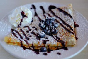 crepe topped with blueberry sauce powdered sugar fresh blueberries and whipped cream