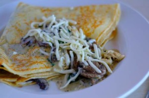 crepe topped with mushrooms and shredded cheese