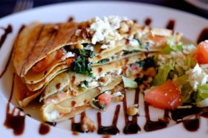 crepe stuffed with colorful vegetables and topped with feta cheese and basalmic sauce