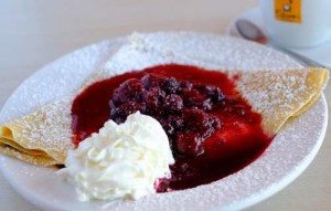 crepe topped with berries in sauce powdered sugar and whipped cream