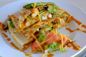 crepe stuffed with chicken and colorful vegetables topped with avacado and shredded cheese